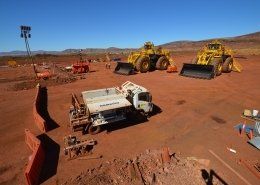 A wide photograph of a mine site, with the Komatsu PC700 loaders